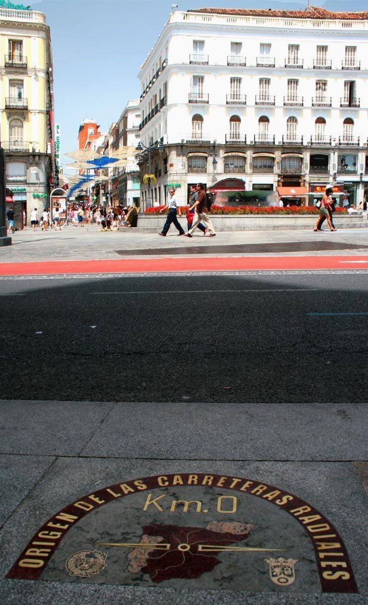 Placa del Km 0 de Madrid, con Sol y Calle Preciados al fondo.